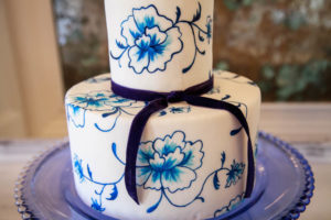 Blue pops of color and floral patterned wedding cake. Scandi-inspired wedding event design.