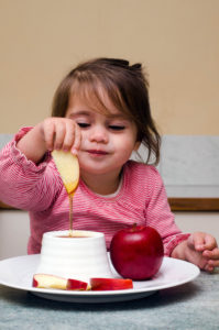 Girl dipping apple honey Rosh Hashanah