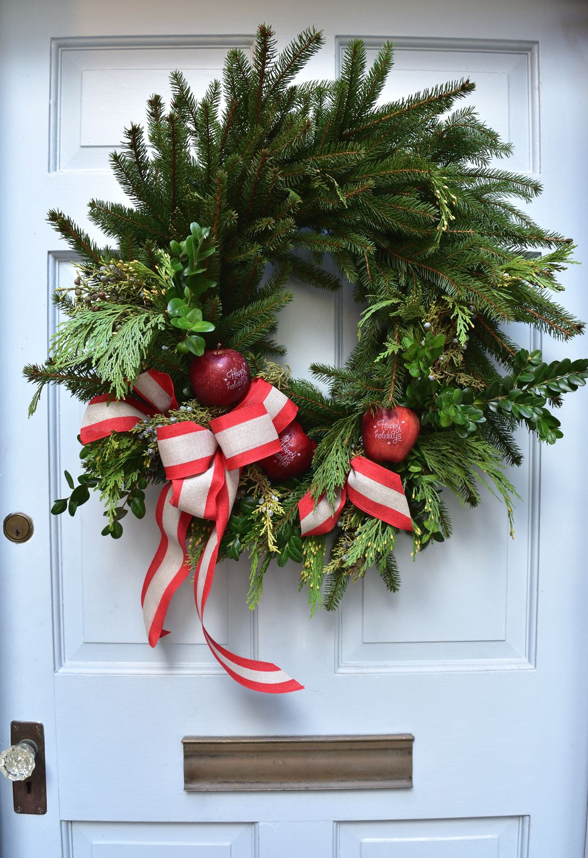 Create your very own holiday wreath for Christmas! Add some Fun to Eat Fruit personalized apples for the wow factor! Check out our blog on FuntoEatFruit.com for styling info by GiggleLiving.com! #wreath #Christmas #brandedfruit #holidaydecor #diy