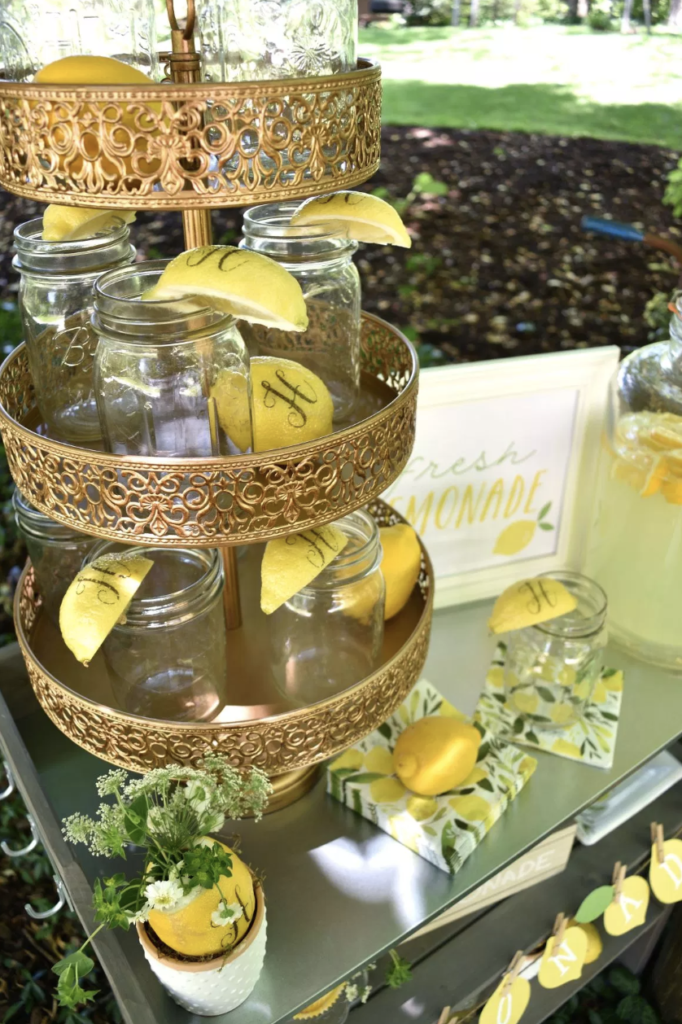 Looking for a new twist on the old fashioned lemonade stand for your next summer party? Learn some tips from Lori of GiggleLiving.com. She shows us how to use Fun to Eat Fruit monogrammed lemons in 4 amazing ways! www.funtoeatfruit.com #lemons #lemonade #lemonadestand #summerpartyideas #partyideas #masonjars #garnishes